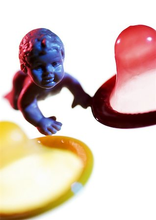 Plastic baby doll between condoms, close-up Stock Photo - Premium Royalty-Free, Code: 695-03384284