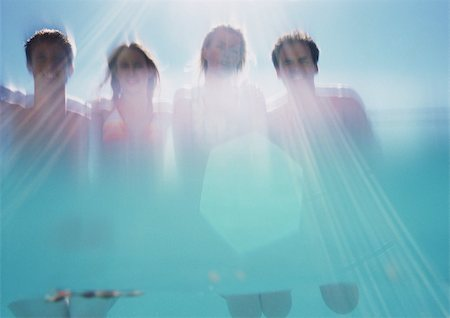 Two men and two women, low angle view, shot from underwater Stock Photo - Premium Royalty-Free, Code: 695-03385121