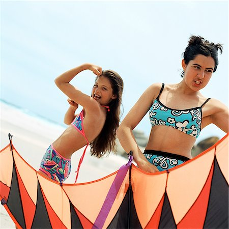 Girl in bathing suit flexing arm muscles, teenager holding kite at the beach Stock Photo - Premium Royalty-Free, Code: 695-03385268