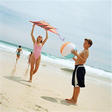 Teenage boy holding beach ball, girl holding kite at the beach Stock Photo - Premium Royalty-Free, Code: 695-03385271
