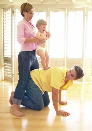 Man on all fours, woman holding baby on his back Stock Photo - Premium Royalty-Free, Code: 695-03385305