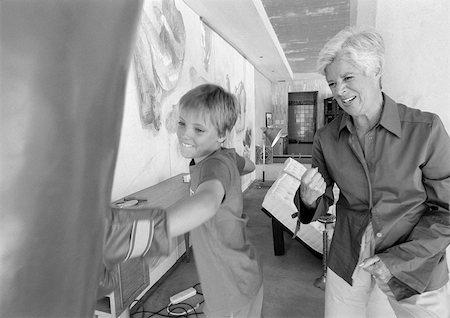 Child hitting punching bag, senior woman cheering him on, b&w Stock Photo - Premium Royalty-Free, Code: 695-03385375