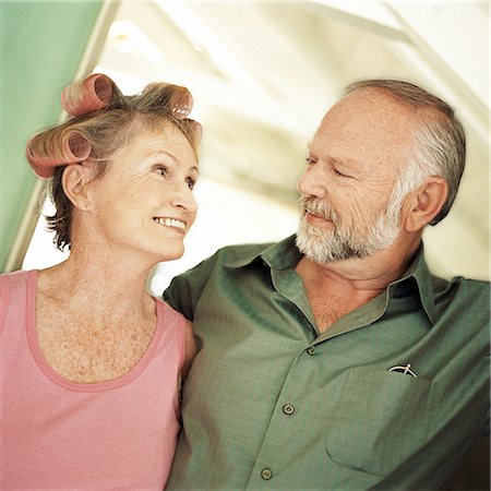 Mature couple looking at each other, woman with rollers in hair, portrait Stock Photo - Premium Royalty-Free, Code: 695-03385426