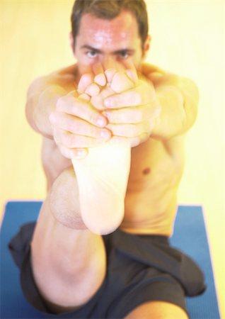 feet gymnast - Man stretching leg on mat, front view Stock Photo - Premium Royalty-Free, Code: 695-03385557