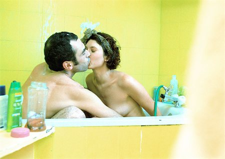 Couple sitting in bathtub, kissing, side view. Stock Photo - Premium Royalty-Free, Code: 695-03385901