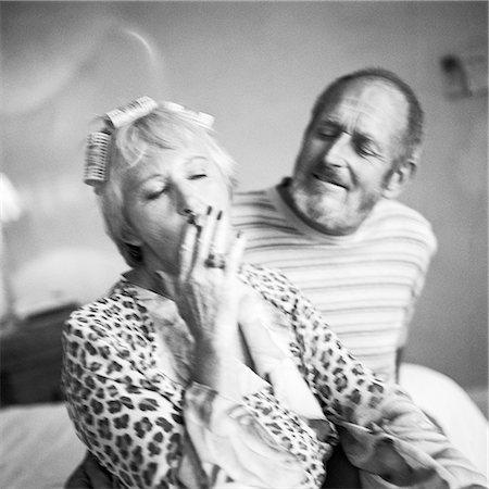 Mature couple sitting, woman smoking cigarette, b&w Stock Photo - Premium Royalty-Free, Code: 695-03385985