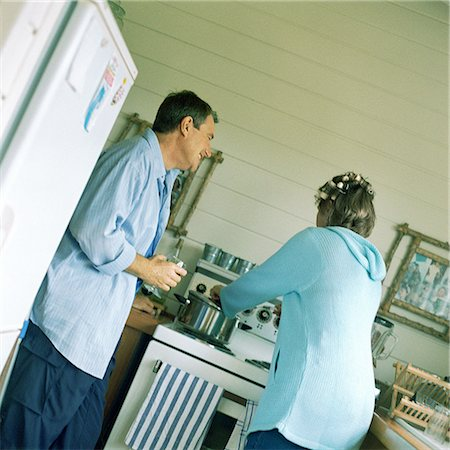 Mature couple in kitchen, woman cooking Stock Photo - Premium Royalty-Free, Code: 695-03385982