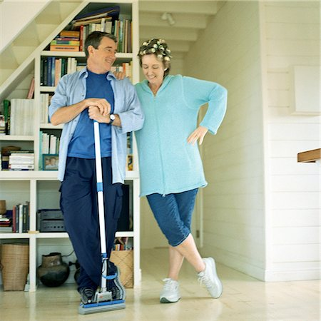Mature couple standing side by side, man holding broom Stock Photo - Premium Royalty-Free, Code: 695-03385983