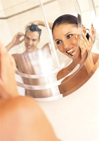 Couple looking at each other in mirror in bathroom Stock Photo - Premium Royalty-Free, Code: 695-03386522