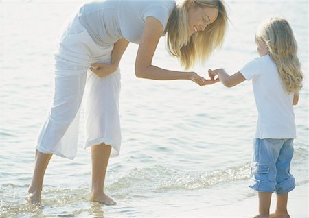 Mother holding hand out to girl on beach Stock Photo - Premium Royalty-Free, Code: 695-03388275