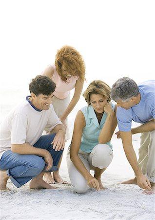 Two mature couples crouching on beach Stock Photo - Premium Royalty-Free, Code: 695-03388723