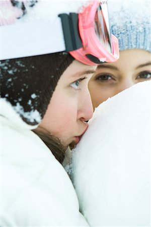 Teenage girl kissing snowball, close-up, friend in background Stock Photo - Premium Royalty-Free, Code: 695-03389295