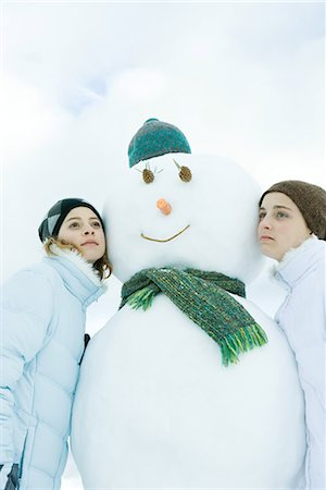 Two young friends leaning against snowman, looking away, portrait Stock Photo - Premium Royalty-Free, Code: 695-03389296
