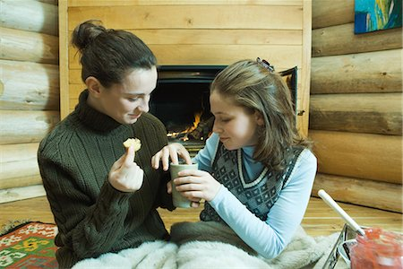 sweater and fireplace - Two teenage girls sitting by fireplace, sharing snack Stock Photo - Premium Royalty-Free, Code: 695-03389346