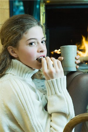 sweater and fireplace - Teenage girl sitting next to fireplace, eating snack, looking at camera Stock Photo - Premium Royalty-Free, Code: 695-03389349