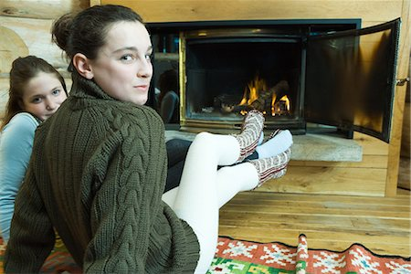 sweater and fireplace - Two teenage girls sitting by fireplace, smiling at camera Stock Photo - Premium Royalty-Free, Code: 695-03389358