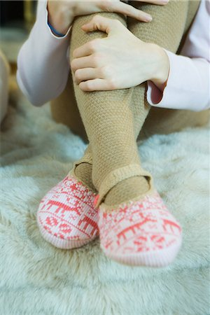 stocking feet - Teenage girl hugging knees, wearing tights and slippers, cropped view of legs Stock Photo - Premium Royalty-Free, Code: 695-03389371