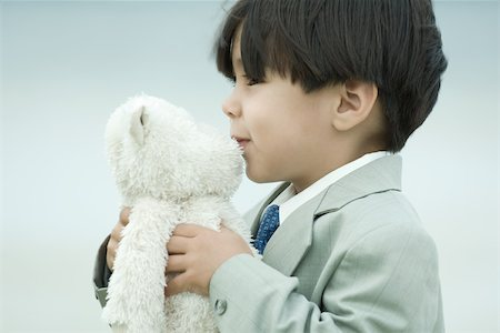 people kissing little boys - Little boy in suit kissing teddy bear Stock Photo - Premium Royalty-Free, Code: 695-03389685