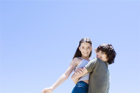 Teenage boy picking up little sister, hugging, low angle view Stock Photo - Premium Royalty-Free, Code: 695-03389797
