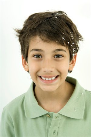 Boy with confetti in his hair, smiling, portrait Stock Photo - Premium Royalty-Free, Code: 695-03389853
