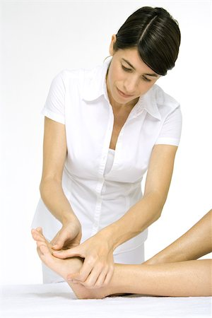 foot massage - Woman giving a foot massage, cropped view of woman's legs Stock Photo - Premium Royalty-Free, Code: 695-03389959