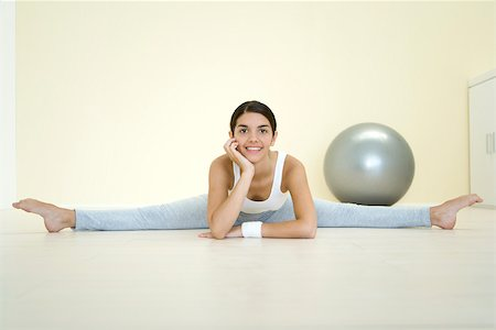 Young woman doing split on the ground, smiling at camera Stock Photo - Premium Royalty-Free, Code: 695-03380079