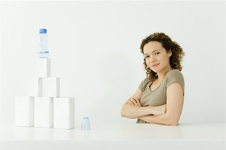Woman beside stacked milk cartons and baby bottle, arms folded, smiling at camera Stock Photo - Premium Royalty-Free, Code: 695-03380146