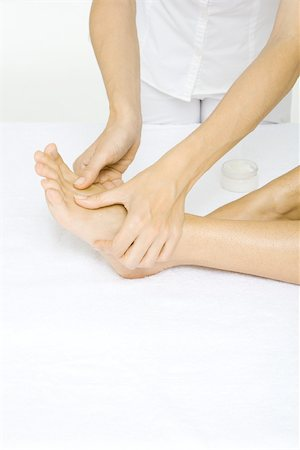foot massage - Woman receiving foot massage, cropped view Stock Photo - Premium Royalty-Free, Code: 695-03380205