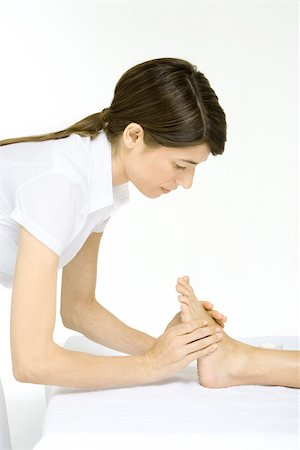 foot massage - Massage therapist performing foot massage, cropped view Stock Photo - Premium Royalty-Free, Code: 695-03380206