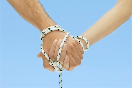 Man and woman holding hands, tied together with rope, cropped view Stock Photo - Premium Royalty-Free, Code: 695-03380288