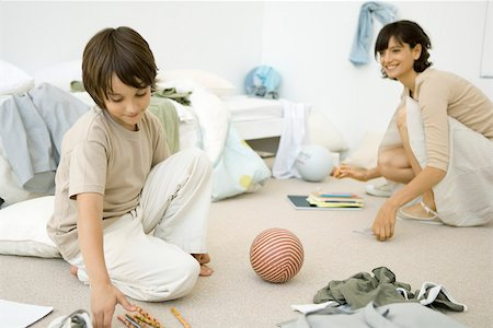 Mother and son crouching down to clean up messy room Stock Photo - Premium Royalty-Free, Code: 695-03380350