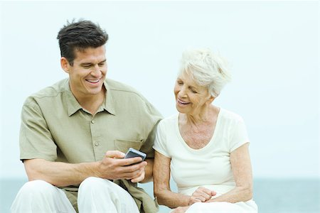 daily - Senior woman with adult son looking at his wireless device Stock Photo - Premium Royalty-Free, Code: 695-03380397