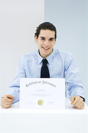 stamp (imprinted mark) - Young man receiving certificate of achievement Stock Photo - Premium Royalty-Free, Code: 695-03380461