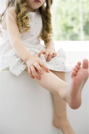 Little girl sitting on ledge with one leg out, cropped view Stock Photo - Premium Royalty-Free, Code: 695-03380478