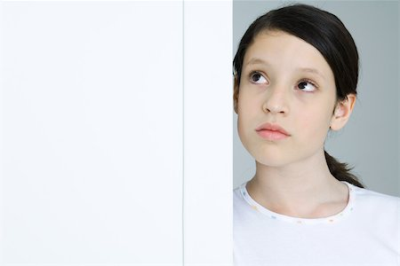sad girls - Girl leaning against doorway, looking up, portrait Stock Photo - Premium Royalty-Free, Code: 695-03380551