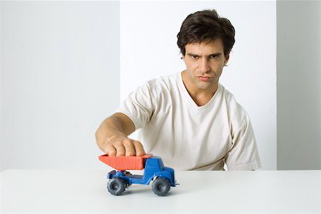 Man playing with toy dump truck, looking at camera with furrowed brow Stock Photo - Premium Royalty-Free, Code: 695-03380579