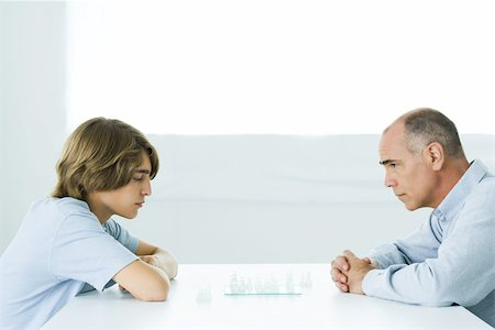 Father and teen son playing chess, side view Stock Photo - Premium Royalty-Free, Code: 695-03380626