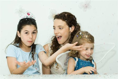 family image and confetti - Girl throwing confetti, mother and sister watching Stock Photo - Premium Royalty-Free, Code: 695-03380664