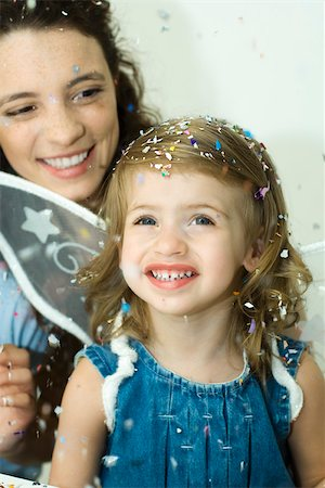 family image and confetti - Little girl watching confetti fall, mother behind her, both smiling Stock Photo - Premium Royalty-Free, Code: 695-03380665