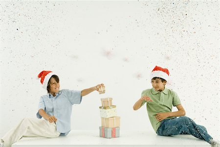 Two boys wearing Santa hats stacking presents, confetti falling around them Stock Photo - Premium Royalty-Free, Code: 695-03380668