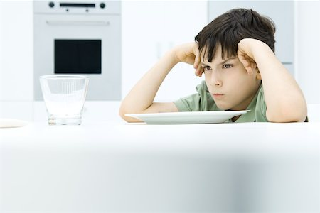 Boy sitting at dinner table, holding head, sulking Stock Photo - Premium Royalty-Free, Code: 695-03380693