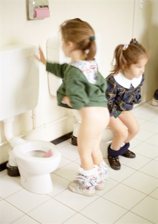 Two little girls using children's toilets Stock Photo - Premium Royalty-Free, Code: 695-03381153