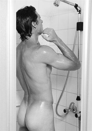 Man taking shower, rear view, b&w Stock Photo - Premium Royalty-Free, Code: 695-03382042