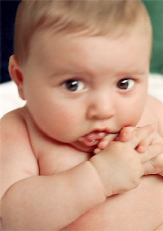 shy baby - Baby looking at camera, hands to mouth, close-up Stock Photo - Premium Royalty-Free, Code: 695-03383375