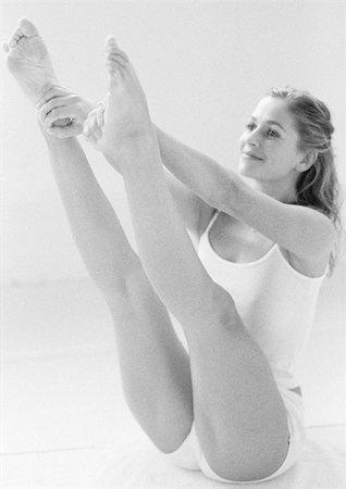 feet gymnast - Woman sitting, extending legs up, holding heels, full length, B&W. Stock Photo - Premium Royalty-Free, Code: 695-03383579
