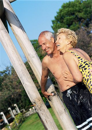 Mature man and woman standing in bathing suits in outdoor shower Stock Photo - Premium Royalty-Free, Code: 695-03383705
