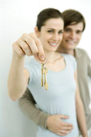 Young couple smiling at camera, woman holding up set of keys Stock Photo - Premium Royalty-Free, Code: 695-03390050