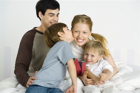 people kissing little boys - Family sitting together on bed, boy kissing mother's cheek Stock Photo - Premium Royalty-Free, Code: 695-03390197