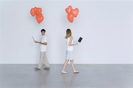 female silhouettes heart - Man and woman walking past each other, both carrying laptop computers and heart balloons Stock Photo - Premium Royalty-Free, Code: 695-03390268