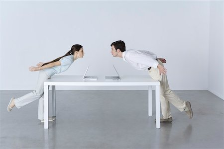 Man and woman at opposite ends of table, leaning towards each other, laptop computers between them Stock Photo - Premium Royalty-Free, Code: 695-03390277